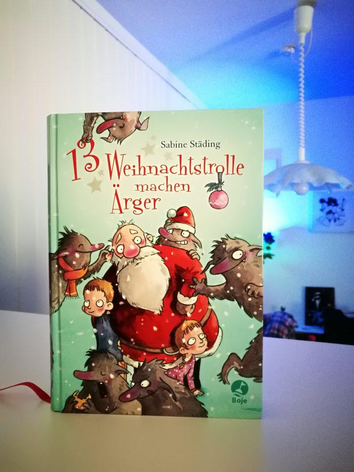Ein Buch-Cover. Bläulich weiss mit Weihnachtsmann, Jonas, Mila und Weihnachtstrolle. 13 Weihnachtstrolle machen Ärger.