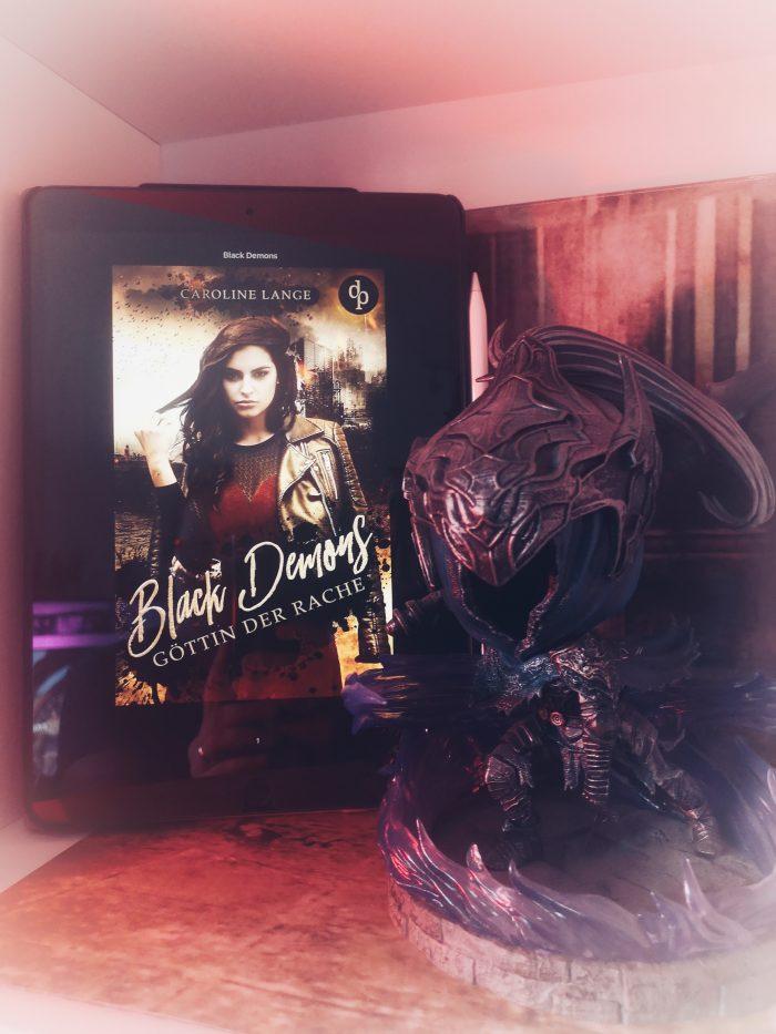 Black Demons - Göttin der Rache. Auf dem Cover ist eine Frau mit roten Kleid und Lederjacke. Daneben eine Damonenfigur.